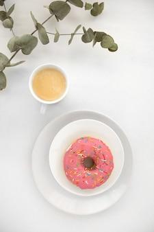 Plant twig near coffee and donut