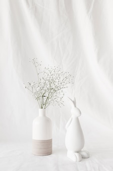 Plant twigs with flowers in vase and figure of rabbit