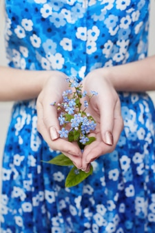 Plant with flowers in girl hand. ecology