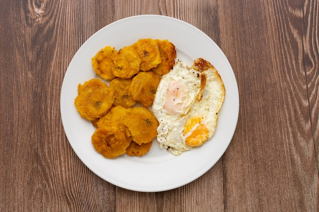 Plantain and fried eggs typical cuban and caribbean food served in white plate on wooden table
