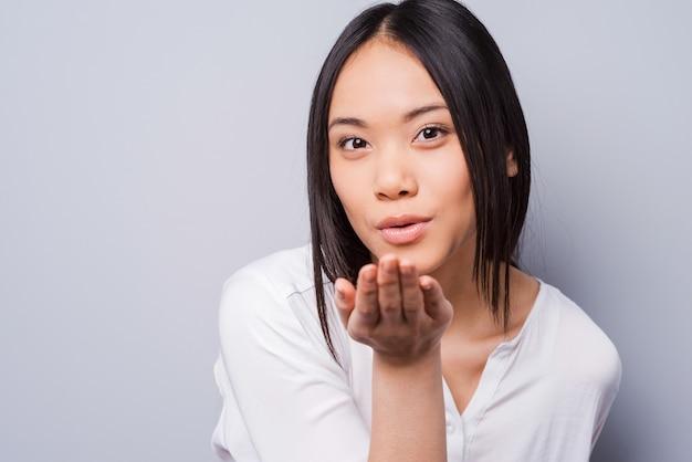 あなたの心にキスを植えます。灰色の背景に立っている間カメラでキスを送信する美しい若いアジアの女性