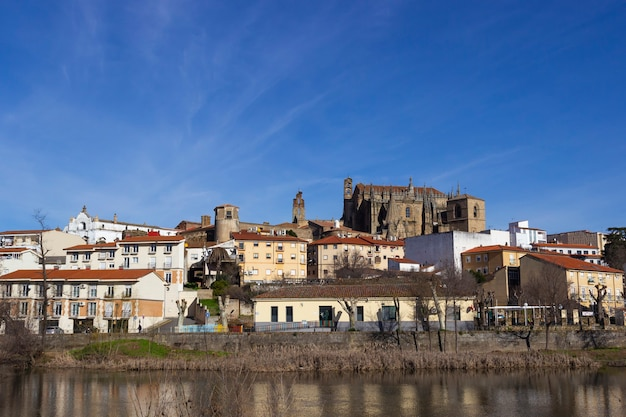 Plasencia city skyline with the jerte river in the foreground and the cathedral and other historic buildings in the background
