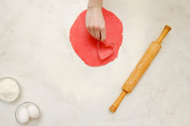 Plast red dough, a female hand with a form for cutting heart. rolling pin, eggs and flour on a white table. space for text. top view