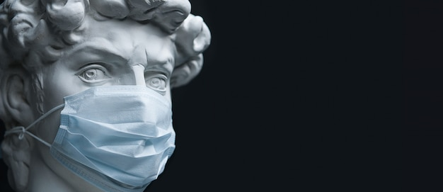 Plaster sculpture in a medical mask. concept of coronavirus epidemics, and the risk of biological contamination. prevention and treatment of influenza.