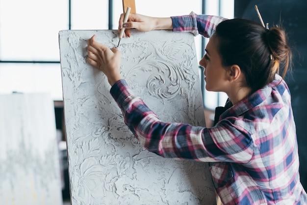 Произведение текстуры гипса. художник женщина с инструментом резьбы. холст на мольберте. талант художника, креативность и воображение.