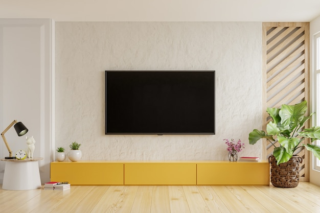 On a plaster wall background a tv is mounted on a yellow cabinet