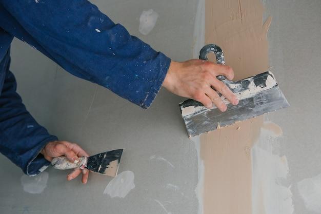 Plasterer男は、青い制服で石膏ボードに2本のはしごをプラスターで仕上げています
