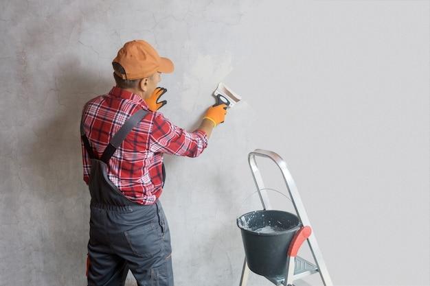 제복을 입은 미장공이 벽에 석고를 바르고 있습니다. 아파트의 개조. 벽을 수리하십시오. 광고, 텍스트를 위한 여유 공간.