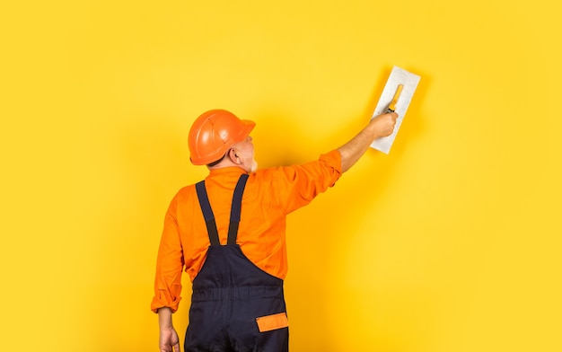 실내 작업 유니폼 석고 벽에 미장입니다. 주걱으로 남자입니다. 퍼티 레이어를 적용하는 과정. 석고용 석고 도구. 노란색 건식 벽체 석고 보드에 석고 흙 주걱입니다.