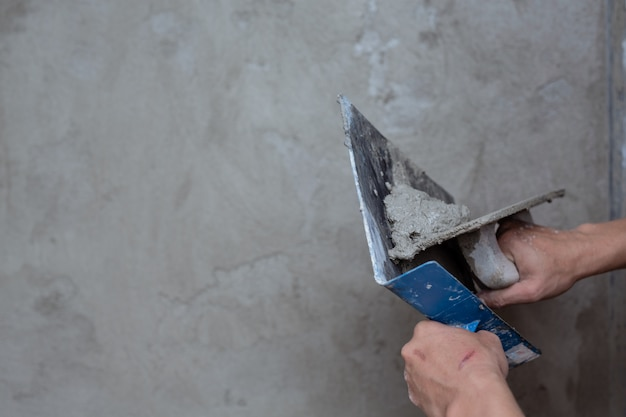 Plasterer renovating indoor walls.