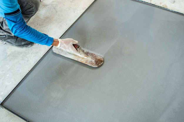 Plastering terrazzo cement with worker in mold