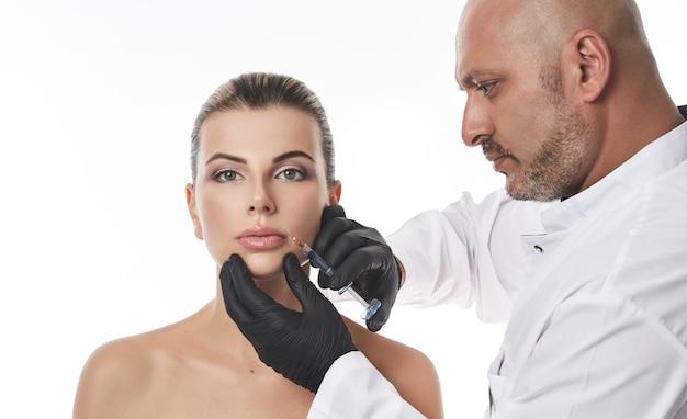플라 스티? 젊은 여자의 입술에 필러 주입을 만드는 외과 의사. 입술 확대 및 교정 개념