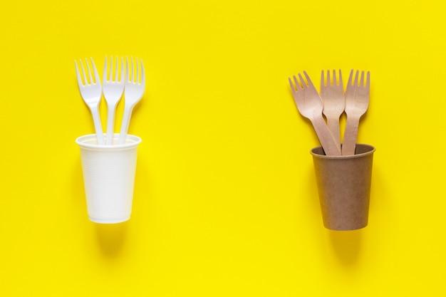 Пластиковая и экологичная одноразовая посуда из бамбука и бумаги на желтом фоне
