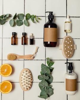 Пластиковые и стеклянные коричневые бутылки с экологически чистой органической косметикой, зеленым эвкалиптом и нарезанными сверху апельсинами. концепция минимализма красоты. натуральные косметические ингредиенты для ухода за кожей.