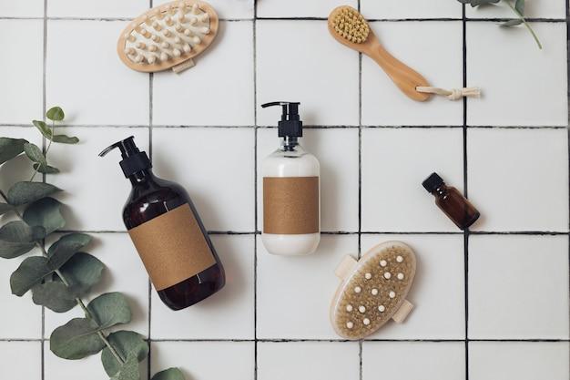 Пластиковые и стеклянные коричневые бутылки с экологически чистой органической косметикой, зеленым эвкалиптом и сверху. концепция минимализма красоты. натуральные косметические ингредиенты для ухода за кожей.