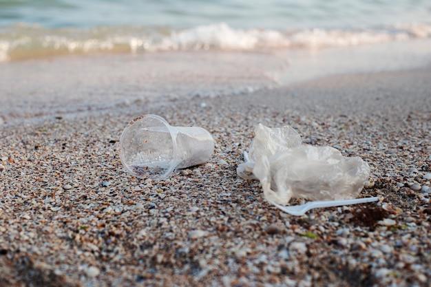 プラスチックとビニール袋、砂浜の背景にゴミ。