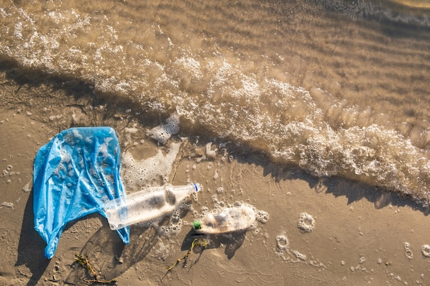 Plastic bag and bottles on the beach, seashore and water pollution concept. trash (empty food package) thrown away at the seaside, top view with waves of water and sand