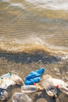 Plastic bag and bottles on the beach, seashore and water pollution concept.