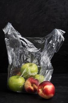 Пластиковый пакет, полный спелых яблок и нектаринов на темно-черном