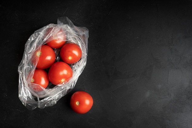 Пластиковый пакет, полный спелых помидоров на темно-черном