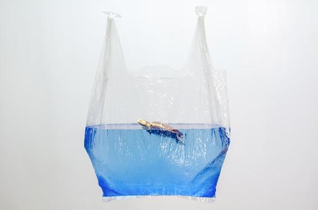 白い背景の水面にぼやけたカメのおもちゃモデルを保持するビニール袋