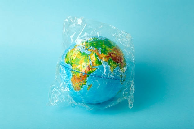 Plastic bag pollution concept. earth globe in a plastic bag on a colored background. plastic and waste pollution oceans, nature