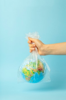 Plastic bag pollution concept. earth globe in a plastic bag on a colored wall