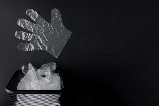 Plastic bag with handles, gloves in the bin on a black background
