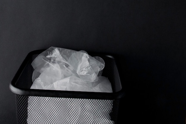 Plastic bag with handles, gloves in the bin on black
