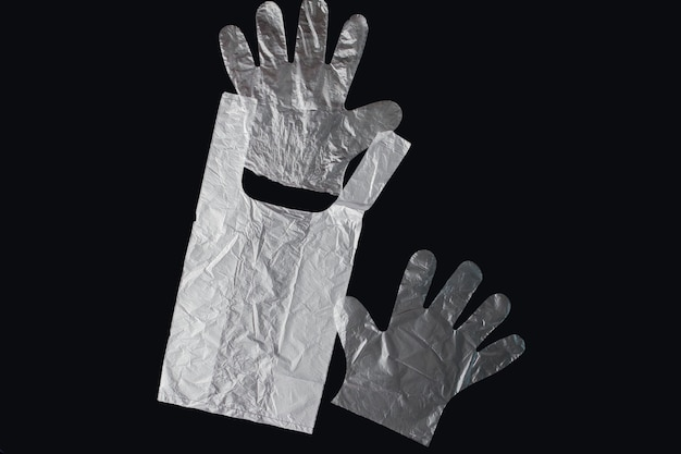 Plastic bag with handles, gloves, on a black background . used plastic bag for recycling. concept - ecology, planet pollution with plastic cellophane polyethylene.