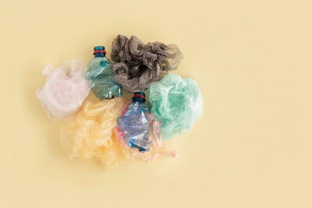 Пластиковые пакеты и бутылки на желтом. нет концепции пластикового мусора.