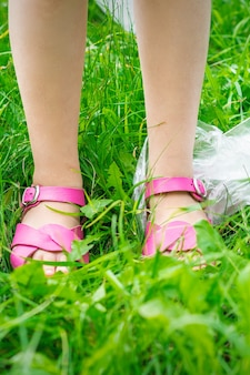 Plastic bags trash with children's feet on green grass while cleaning the park from plastic debris