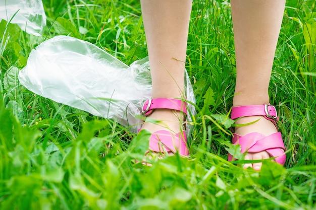ビニール袋は、プラスチックの破片から公園を掃除している間、緑の草の上に子供の足でゴミを捨てます