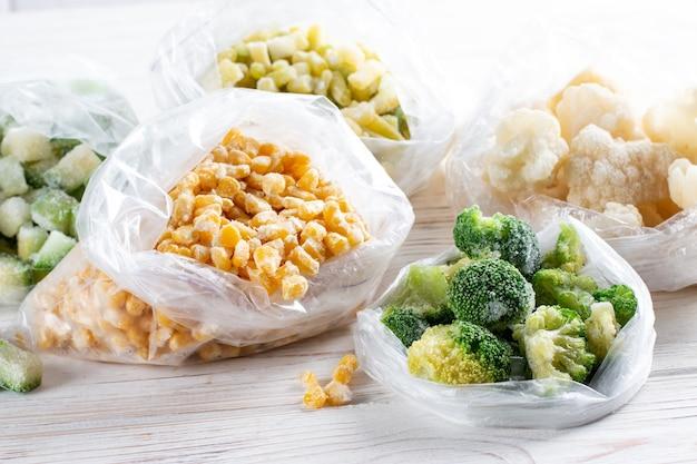 Пластиковые пакеты с замороженными овощами на белом деревянном столе