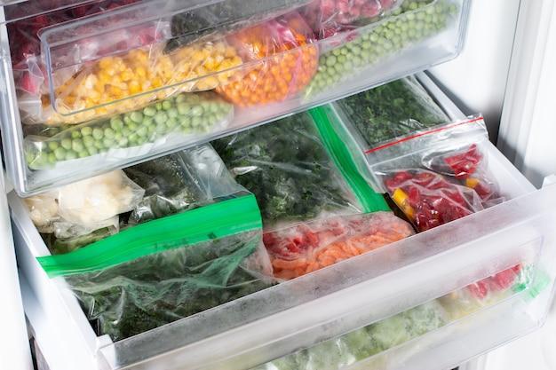 Пластиковые пакеты с различными замороженными овощами в холодильнике. хранение продуктов