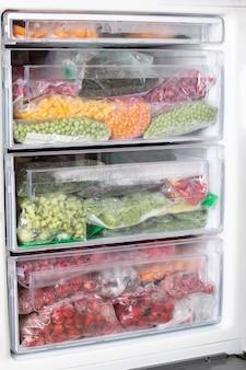 冷蔵庫にさまざまな冷凍野菜が入ったビニール袋。食料貯蔵庫