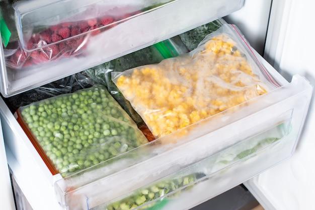 Пластиковые пакеты с различными замороженными овощами в холодильнике.
