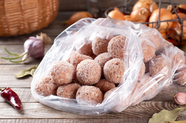 Plastic bags with frozen meat and meatballs in plastic bag on a wooden table