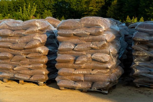 정원 센터에서 운반하기 위해 팔레트에 접힌 경로 및 화단 장식용 오크 나무 껍질과 나무 조각이있는 비닐 봉지