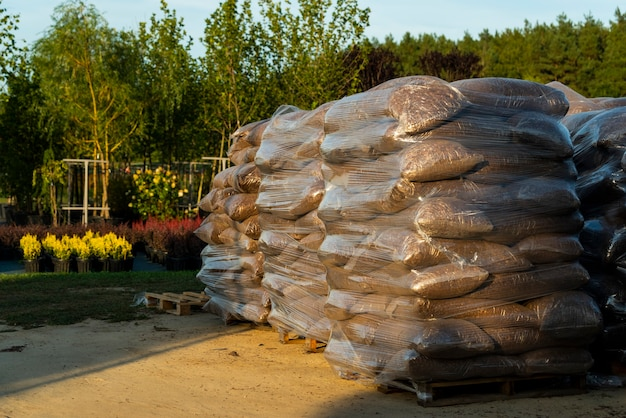 Plastic bags with oak bark and wood chips for decorating paths and flower beds folded on pallets for transportation in the garden center
