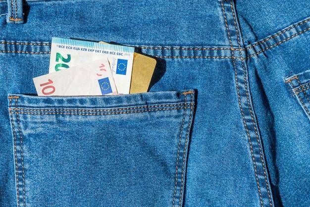 Пластиковая банковская карта с наличными евро в синих джинсах - концепция денег