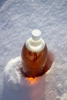 Plastic beer bottle in the snow in winter in nature, beer background.