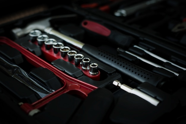 Пластиковый черный контейнер со многими инструментами на столе