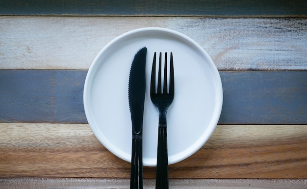 Plastic black fork and knife with empty white dish on vintage wooden plate.