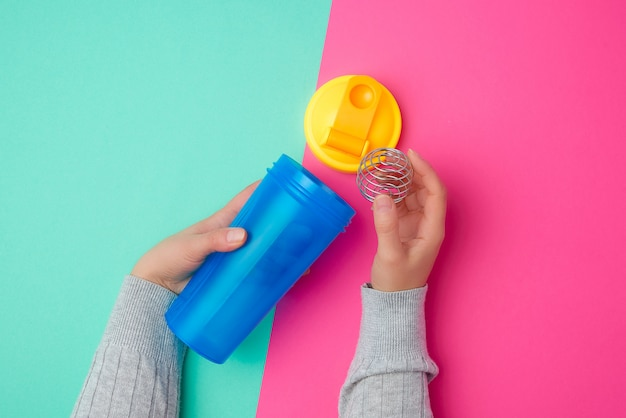 Plastic blue shaker bottle with a yellow cap and an iron ball for sports people