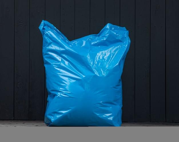 Пластиковый синий мешок для мусора на улице