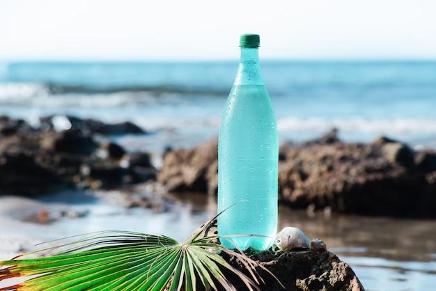 Пластиковая бутылка покрыта каплями на камне