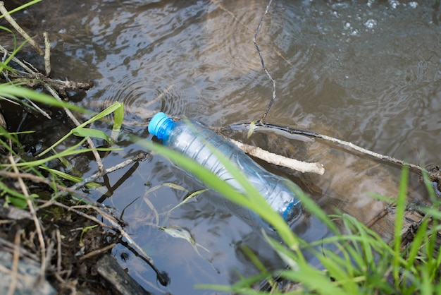 Пластиковая бутылка, плавающая в воде на природе, вид сверху. выброшенный пластиковый мусор в ручье, озеро или реку, на открытом воздухе. загрязнение природы, концепция экологии