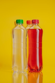 Plastic bottle full of drink on a bright yellow background