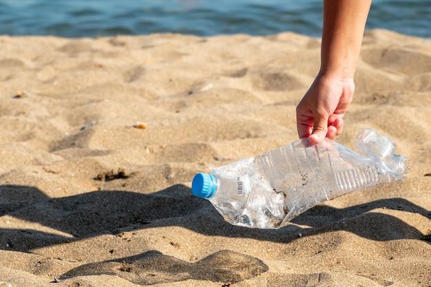 Пластиковая бутылка находится на пляже, оставленном туристом